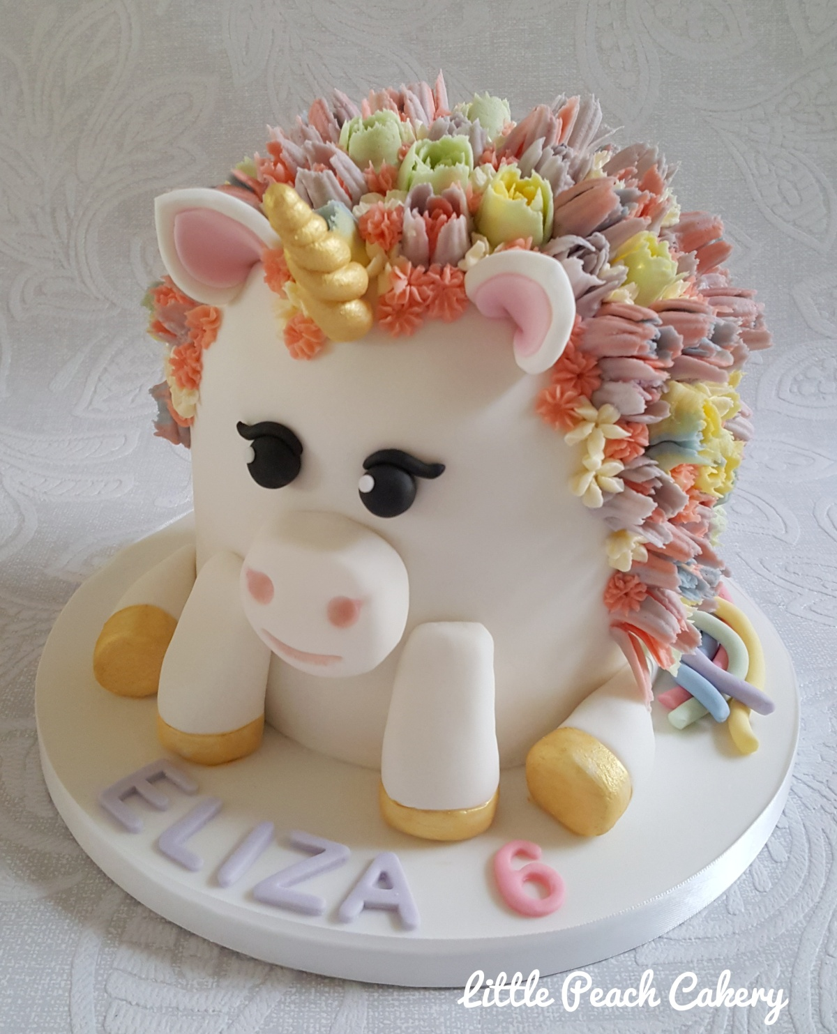Simple 3D sitting unicorn cake with buttercream flower mane